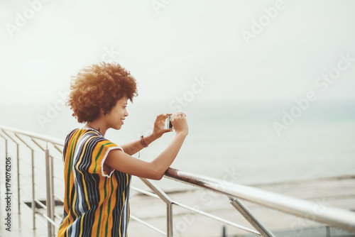 Valokuva  Young curly smiling black girl with afro hair is leaning on wet chrome railing a
