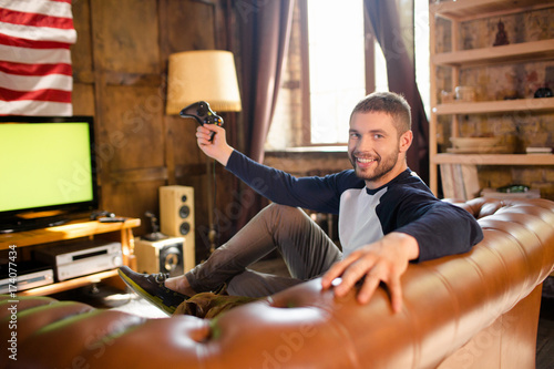 Happy young man sitting on couch holding game controler Canvas Print