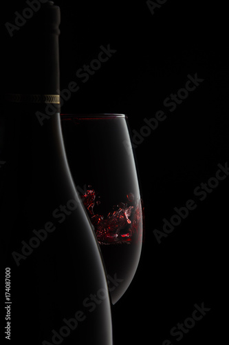 Fotografie, Obraz  A bottle and glass of elegant red wine with splash.