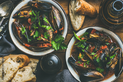 Fotografía  Flat-lay of Belgian boiled mussels in tomato sauce with fresh parsley in serving
