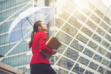 Young Beautiful Asian Business Woman Holding Umbrella And Documents Walking To Office For Working Under Sunlight And Hot Weather.