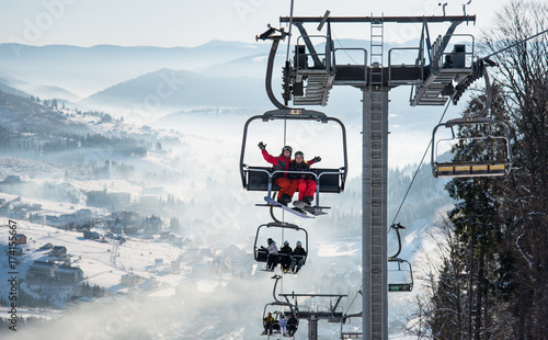 Fototapeta Young Couple Snowboarders Riding Up At Ski Lift At Skiing And Snowboarding Winter Resort In The Mountains Copyspace Lifestyle Vacation