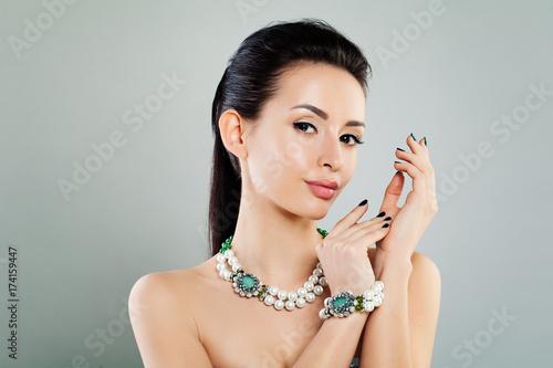Plakat Śliczna kobieta na sztandaru tle. Efektowny makijaż, naszyjniki i bransoletka