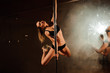 young hot woman in sexy lingerie performs sensual pole dance. Go-go dancer