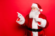 Sales, marketing, discounts, advertising, presents, gifts selling time! Holly jolly x mas is soon! Be ready, prepare! Saint nicholas is showing on side with forefingers, isolated on red background