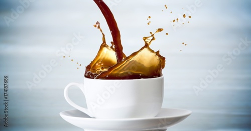 Fotografie, Obraz  Coffee being poured into white cup against blurry blue wood