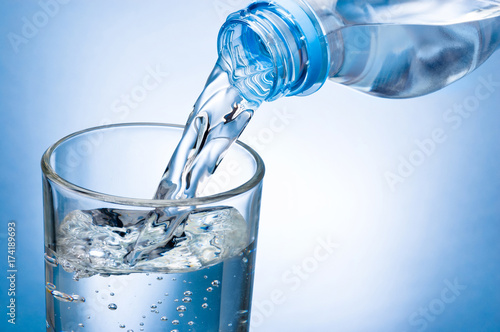 In de dag Water Pouring water from bottle into glass on blue background