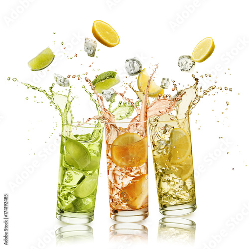 citrus fruits soft drink with fruit slices and ice cubes falling and splashing, on white background Wall mural
