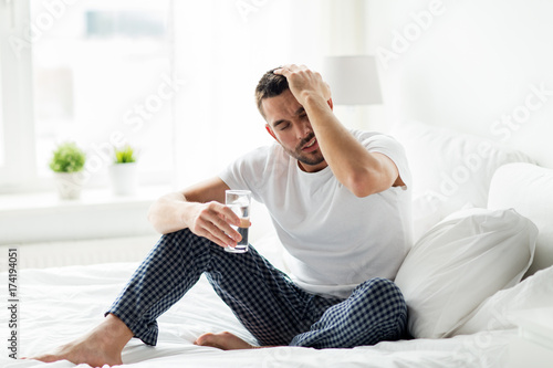 Obraz na plátne man in bed with glass of water at home