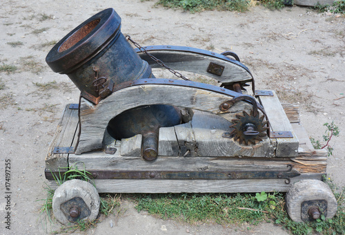 Plakat Zaprawa to urządzenie, które wystrzeliwuje pociski przy małych prędkościach i krótkich zasięgach. Stary zardzewiały moździerz lub pistolet artyleryjski na kółkach. Koncepcja zimnej hybrydy wojny.