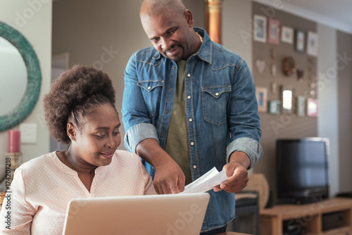 Valokuva  African couple paying bills online together at home