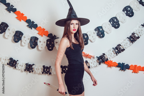 Canvas Prints Art Studio Woman in a witch costume with a knife in her hands. Halloween.