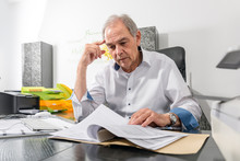 Älterer Mann Mit Weißem Hemd  Sitzt An Einem Schreibtisch Und Blättert In Einer Dokumenten Akte