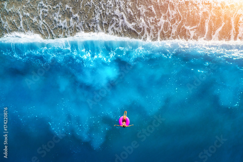 Valokuva  Aerial view of slim woman swimming on the pink swim ring in the transparent turquoise sea in Oludeniz,Turkey