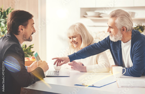 Positive old couple meeting with their insurance agent