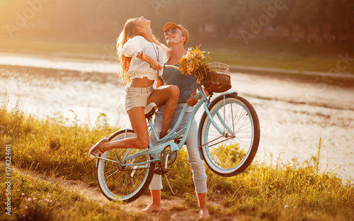 Carta da parati  young couple in love riding a bike near the river in the summer at the weekend