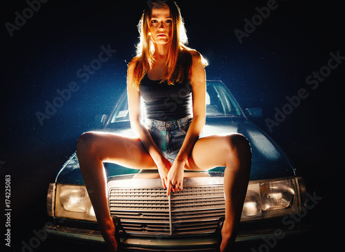 Cuadros en Lienzo ,A beautiful girl in short shorts and high heels is standing by the car at night