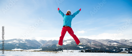 Fotobehang Wintersporten Young woman jumping in the mountains