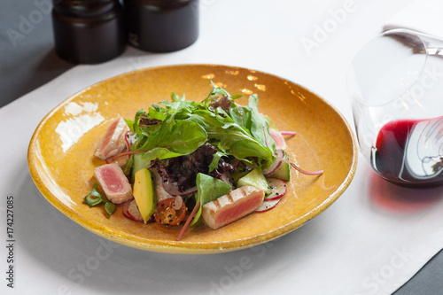 Photo tuna salad with fresh vegetables and a glass of red wine