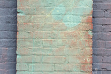 Green And Red Washed Paint On A Brick Column On The Face Of A Purple Painted Wall