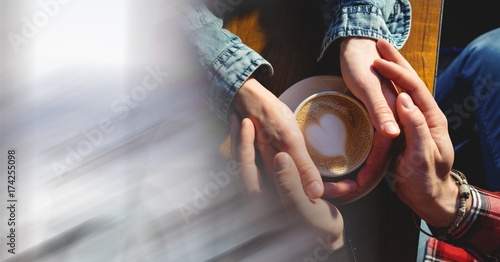 Overhead of two pairs of hands around coffee cup with heart in