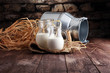 Leinwanddruck Bild A jug of milk and glass of milk on a wooden table