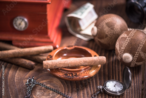 Cuban cigar in ashtray on wooden table Canvas Print