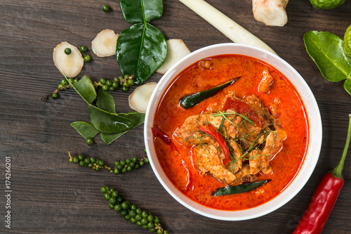 Fototapeta Chicken panang curry and ingredient spice on wooden background in the kitchen, Thai food concept. obraz