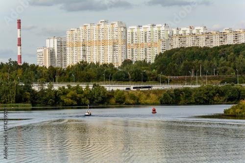 Foto op Plexiglas Stad aan het water Вид на реку с моста - городской пейзаж и лодка