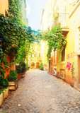 Fototapeta Alley - view of old town italian narrow street with blue sky in Trastevere, Rome, Italy, retro toned