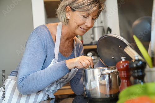 Photo Stands Cooking Senior woman in home kitchen cooking for dinner