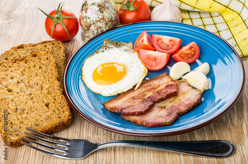 Zdjęcie XXL Jajka sadzone z bekonem, pomidorami i czosnkiem w talerzu, nóż