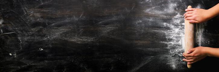 Djevojčice drže valjak s brašnom na tamnocrnom stolu, pozadina za pečenje, pogled odozgo, kopirajte prostor za tekst, meru, recept. Natpis