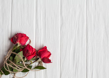 Three Red Roses On A Wooden Wh...