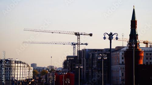 Obraz na płótnie Żurawie wieżowe, dźwigi budowlane w mieście Moskwa, część Kremla i słynny most