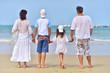 family standing on sandy beach