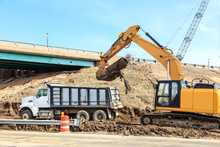 Backhoe And Dump Truck Excavating On A Job Site
