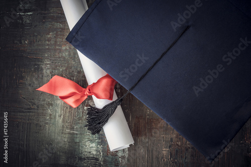 Fototapeta Graduation hat and diploma on table obraz na płótnie