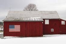 American Flag On Rural Barn In Snowy Landscape
