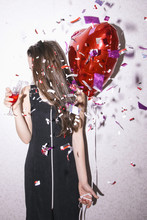Young Woman In Black Dress Holding Red Balloon And Glass Of Champagne