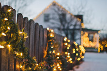 Holiday Lights And Garland Adorn Wooden Fence