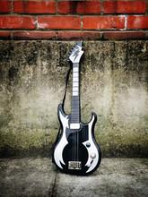 A Toy Guitar Against A Brick Wall