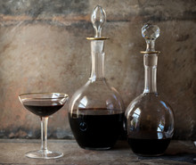 Decanters And Glass Of Red Wine Against Rustic Wall