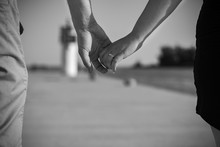 Couple Holding Hands On A Pier