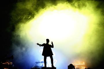 Silhouette of an unrecognizable man singing rap