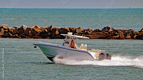 Small open fishing boat powered by two outboard engines speeding through Government Cut on its way to fishing grounds in the open ocean.