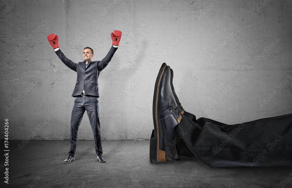 Fototapeta A happy businessman with boxing gloves on arms raised in victory stands near a giant male leg fallen down.
