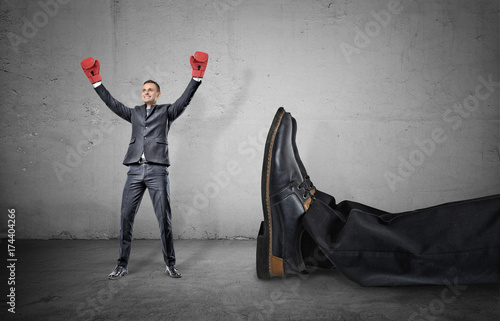 Fotografía  A happy businessman with boxing gloves on arms raised in victory stands near a giant male leg fallen down