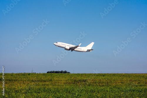 Zdjęcie XXL Zielone pole, błękitne niebo i biały samolot pasażerski startuje
