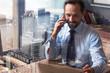 Cheerful confident businessman talking on phone